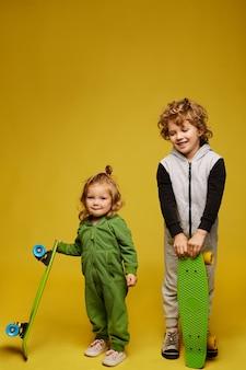 Heureux enfant bouclé et mignonne petite fille en kigurumi tenant des longboards et posant