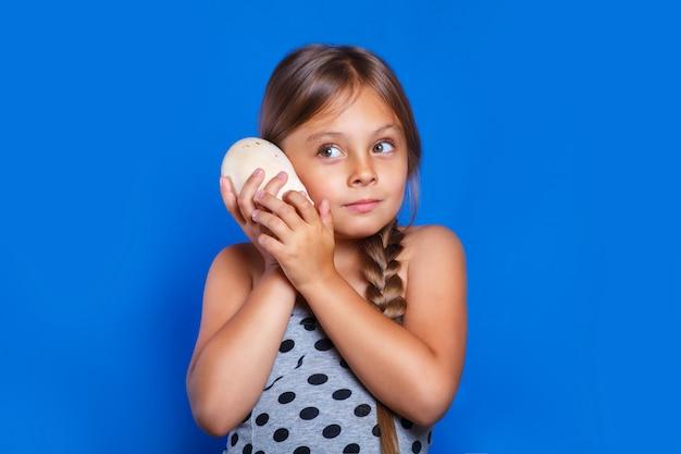 Heureux enfant écoute coquillage. vacances d'été et concept de voyage