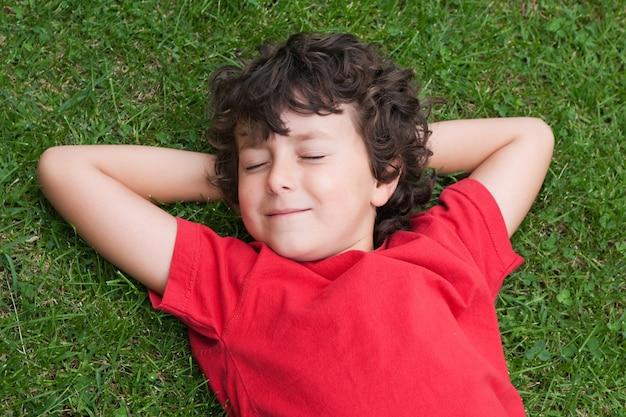 Heureux enfant endormi sur l'herbe avec une chemise rouge