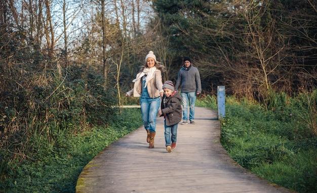 Heureux enfant et femme se tenant la main et courant sur un sentier en bois tandis que l'homme regarde en arrière-plan