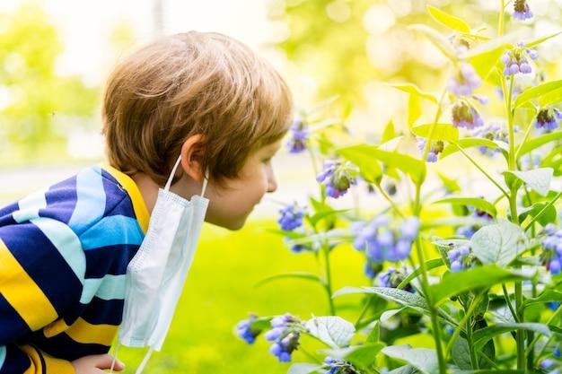 Heureux enfant garçon enlevant son masque de protection médical et respirant l'air sentant les fleurs pulmonaria