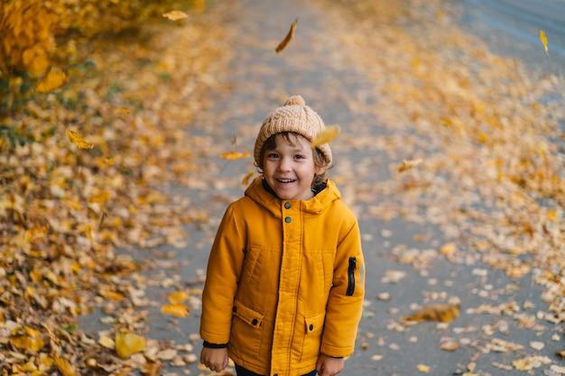 Heureux enfant garçon riant et jouant dans la journée d'automne.