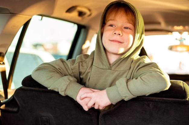 Heureux enfant à l'intérieur de la voiture lors d'un voyage sur la route