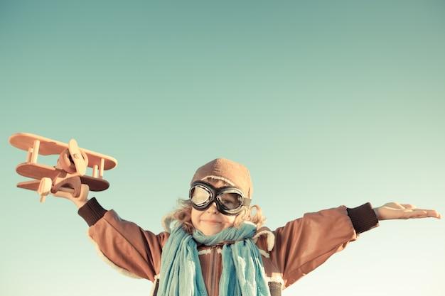 Heureux enfant jouant avec un avion en bois jouet sur fond de ciel d'automne. rétro tonique