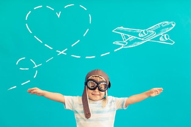 Heureux enfant jouant avec un avion en bois vintage contre le mur bleu.