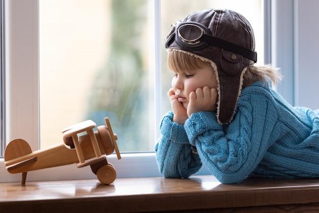 Heureux enfant jouant avec un avion en bois vintage à l'intérieur.