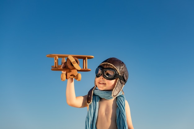 Heureux enfant jouant avec un avion en bois vintage. kid s'amusant en plein air sur fond de ciel d'été