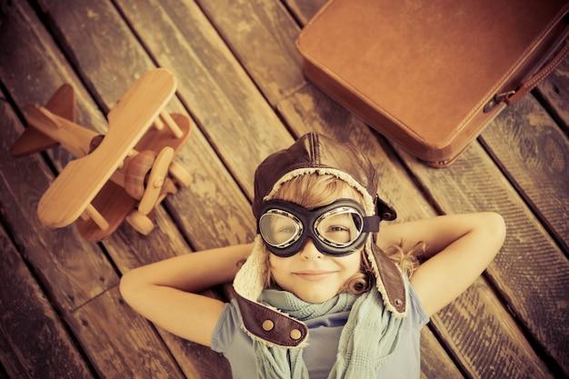 Heureux enfant jouant avec un avion jouet à la maison. rétro tonique