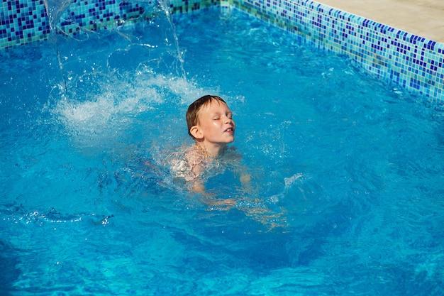 Heureux enfant jouant dans l'eau bleue de la piscine sur une station balnéaire tropicale à la mer