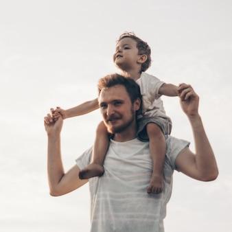 Heureux enfant jouant avec le père. papa et fils à l'extérieur. père portant l'enfant sur le dos. héhé dans le domaine de l'été.