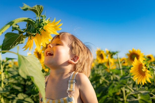 Heureux enfant jouant avec le tournesol en plein air. kid s'amusant dans le champ de printemps vert sur fond de ciel bleu.