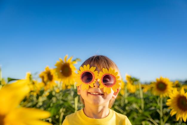 Heureux enfant jouant avec le tournesol en plein air