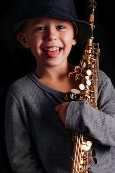 Heureux enfant joue du saxophone en studio