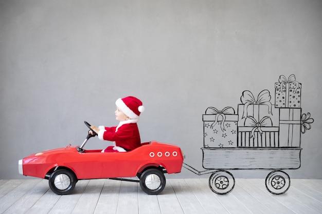 Heureux enfant payant à la maison. enfant s'amusant le temps de noël. concept de vacances de noël