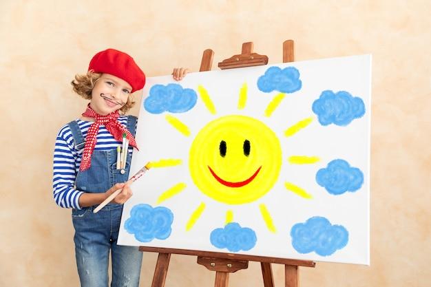 Heureux enfant peignant le soleil et les nuages sur toile.