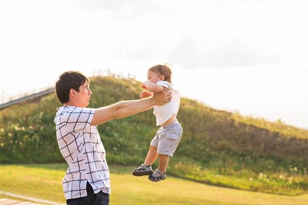 Heureux enfant, père et fils s'amusant, tenant les mains sur un coucher de soleil au soleil