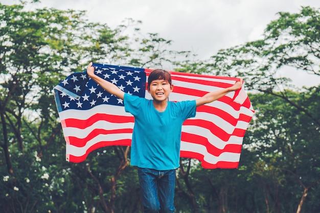 Heureux enfant petit enfant courir avec le drapeau américain les états-unis célèbrent le 4 juillet