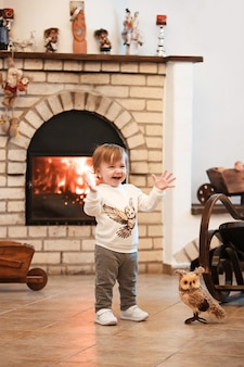 Heureux enfant petite fille debout à la maison contre cheminée