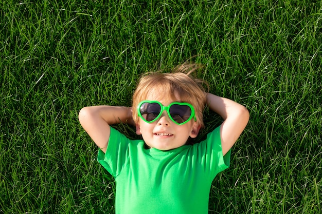 Heureux enfant portant sur l'herbe verte