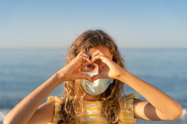Heureux enfant portant un masque médical en plein air contre le ciel bleu.