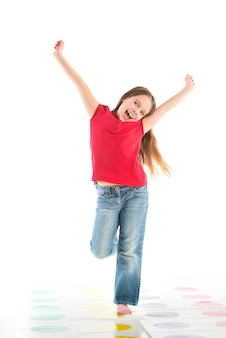 Heureux enfant posant dans des vêtements pour enfants debout sur une jambe, les bras levés