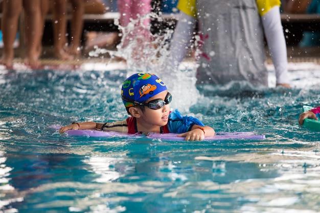 Heureux enfant qui joue dans la piscine.