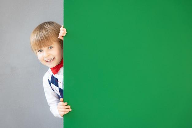 Heureux enfant se cachant derrière un tableau vert.
