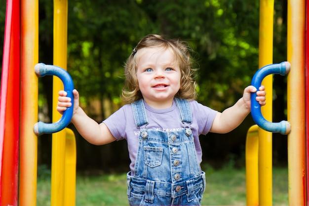 Heureux enfant souriant jouant dans une aire de jeux