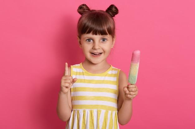 Heureux enfant souriant tenant la crème glacée et pointant vers le haut avec son index, vêtu d'une robe d'été avec des rayures blanches et jaunes.