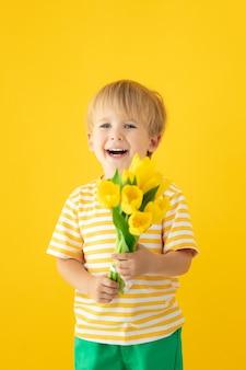 Heureux enfant tenant le bouquet de printemps de tulipes contre le mur jaune.