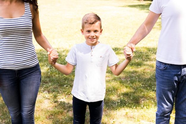 Heureux enfant tenant les mains de ses parents