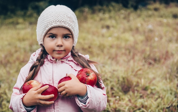 Heureux enfant tenant des pommes rouges dans ses mains. harvest funny kid à l'extérieur dans le parc de l'automne.