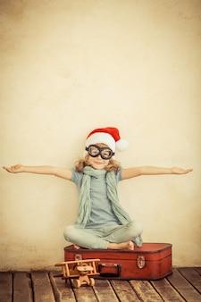 Heureux enfant vêtu d'un chapeau de père noël. enfant jouant avec un avion jouet à la maison. rétro tonique