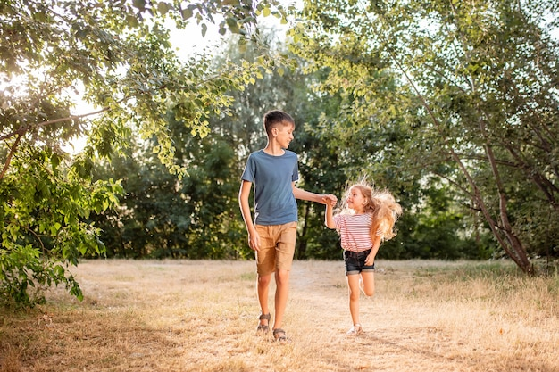 Heureux enfants garçon et fille gambader dans le parc. le frère aîné joue avec sa sœur dans la nature dans les rayons du soleil couchant d'une journée d'été.