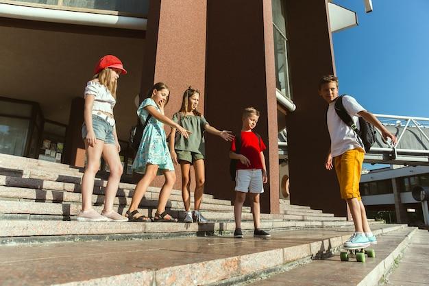 Heureux les enfants jouant dans la rue de la ville en journée d'été ensoleillée devant un bâtiment moderne