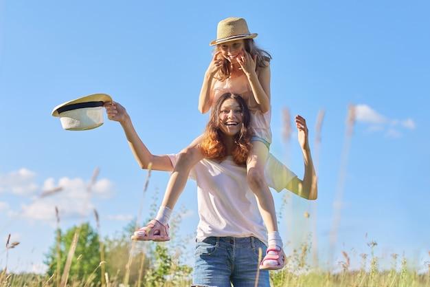 Heureux enfants riant jouant dans le pré, deux filles soeur s'amusant dans la nature