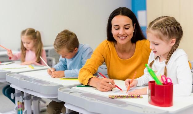 Heureux enseignant aidant ses élèves