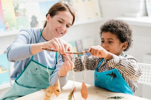 Heureux enseignant et écolier tenant un bâton avec des décorations d'halloween tout en les préparant pour les vacances à la leçon