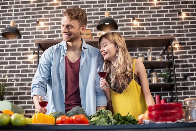 Heureux ensemble. jeune couple d'amoureux juste marié riant et se sentant heureux de cuisiner ensemble