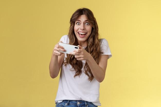 Heureux enthousiaste excité jolie fille ludique gagner un jeu de smartphone génial ravi de jouer à la caméra de regard surpris triomphant souriant joyeusement tenir le téléphone mobile sur fond jaune horizontal