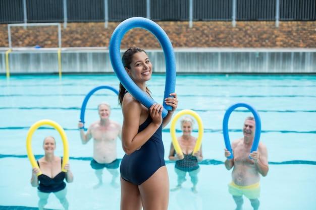 Heureux entraîneur féminin et nageurs seniors tenant des nouilles de piscine