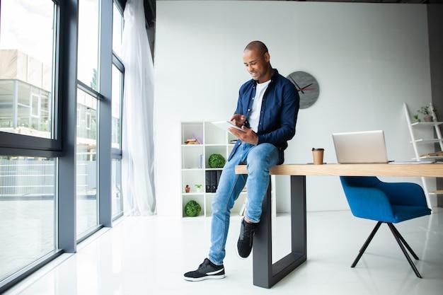 Heureux entrepreneur afro-américain à l'aide d'une tablette tactile.