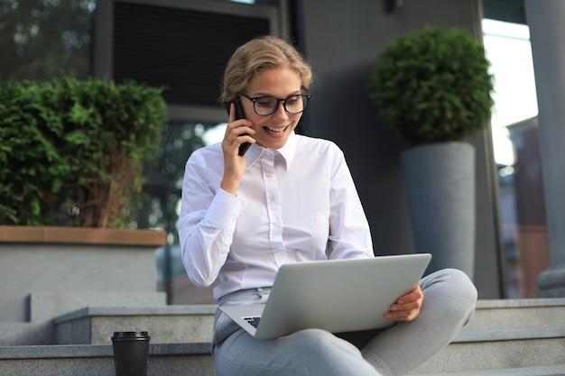 Heureux entrepreneur travaillant avec un téléphone et un ordinateur portable près du bureau.