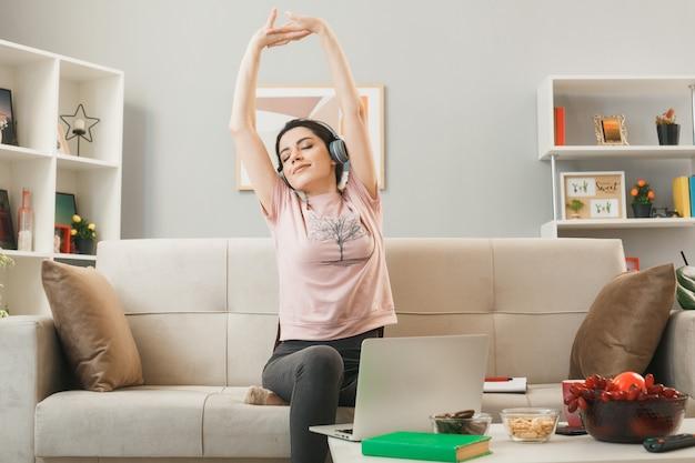 Heureux d'étirer le bras jeune fille portant des écouteurs assis sur un canapé derrière une table basse dans le salon
