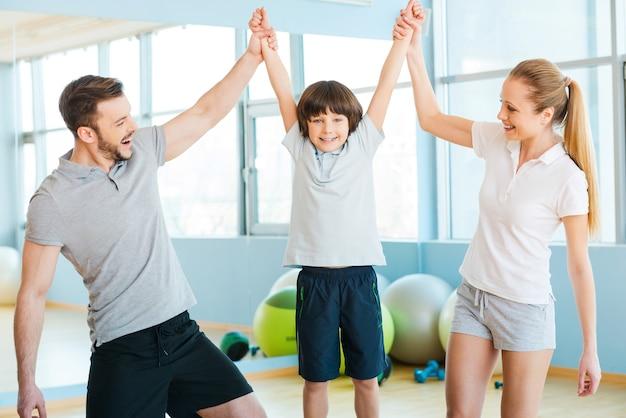 Heureux d'être en bonne santé. heureux père et mère s'amusant avec leur fils dans un club de remise en forme avec des balles de fitness posées en arrière-plan
