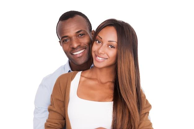 Heureux d'être ensemble. beau jeune couple africain debout près l'un de l'autre et souriant à la caméra tout en isolé sur blanc