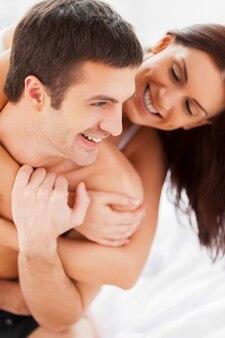 Heureux d'être ensemble. beau jeune couple d'amoureux s'amusant assis ensemble dans son lit