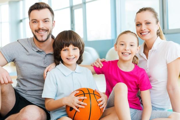 Heureux d'être une famille. bonne famille sportive se liant les uns aux autres tout en étant assis ensemble dans un club de sport