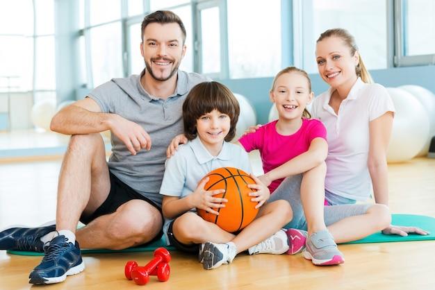 Heureux d'être une famille. bonne famille sportive se liant les uns aux autres tout en étant assis sur un tapis d'exercice ensemble