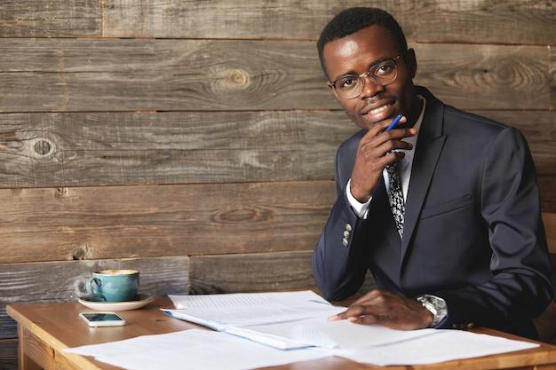 Heureux étudiant africain en costume formel et lunettes à la recherche et souriant